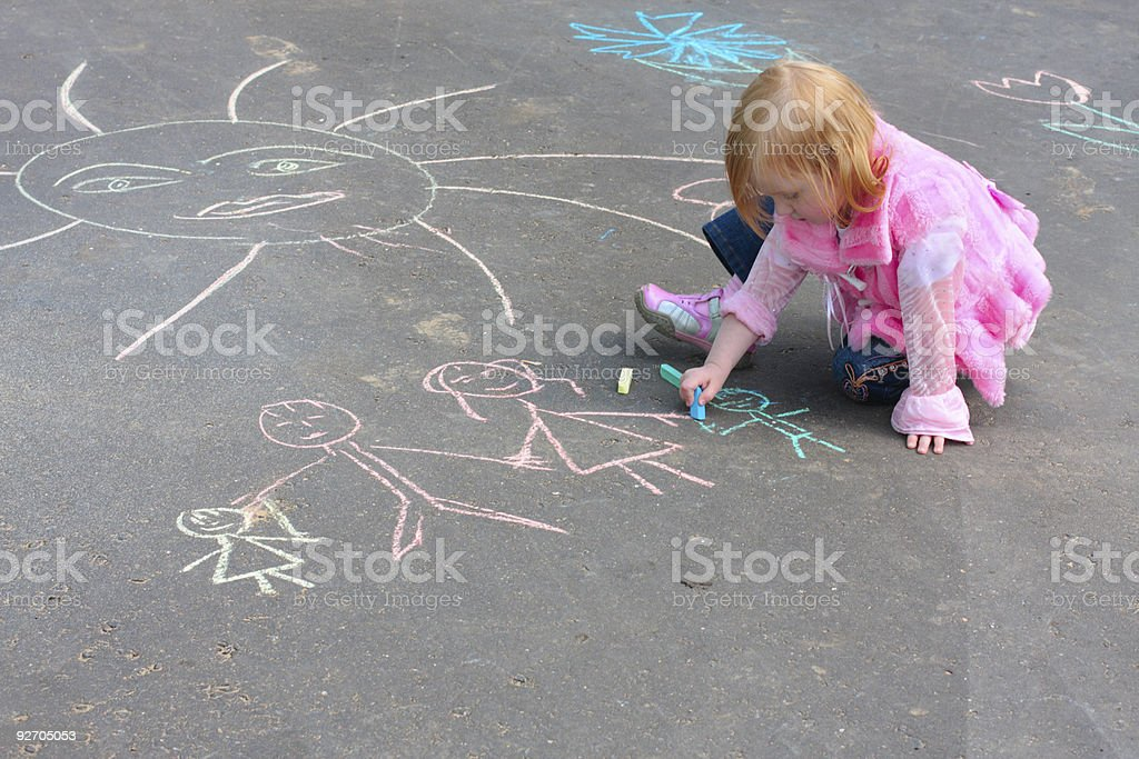 Little girl wearing pink using chalk on asphalt royalty-free stock photo