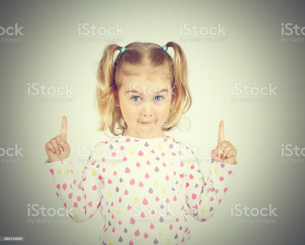 little girl wearing  pointing by forefinger to somewhere up stock photo