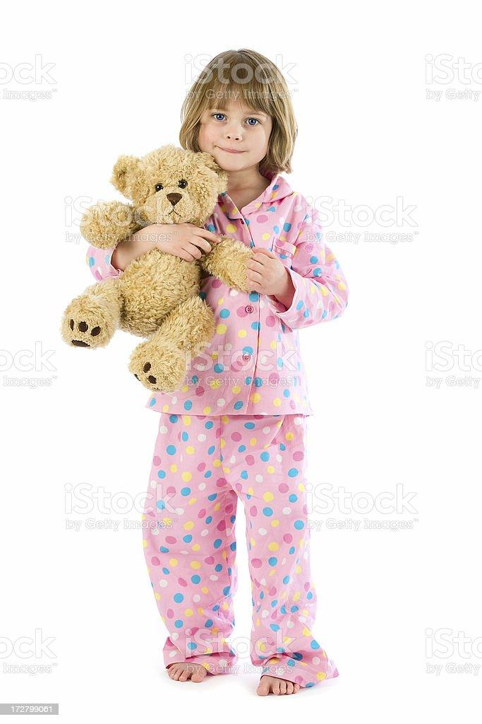 Little girl wearing pyjamas holding teddy on white stock photo