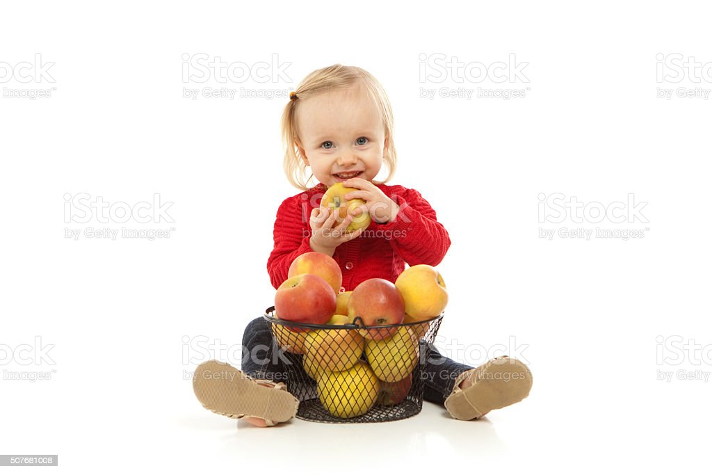 Little Girl Wearing Red Sweater Eating Apple on White Background stock photo