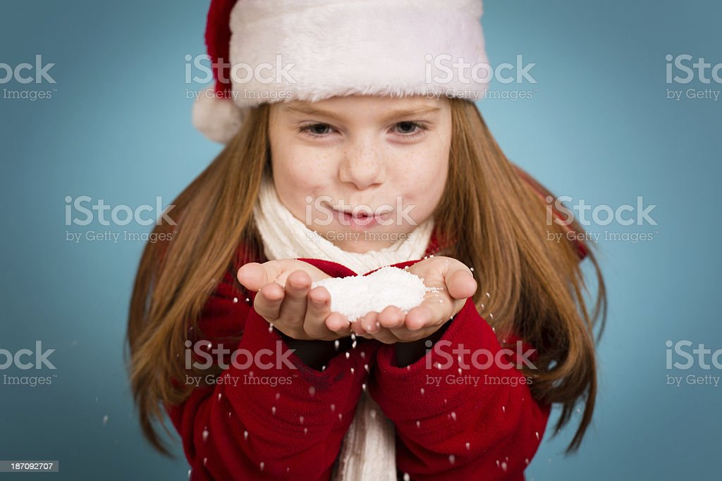 Little Girl Wearing Santa Hat and Holding Handful of Snow royalty-free stock photo