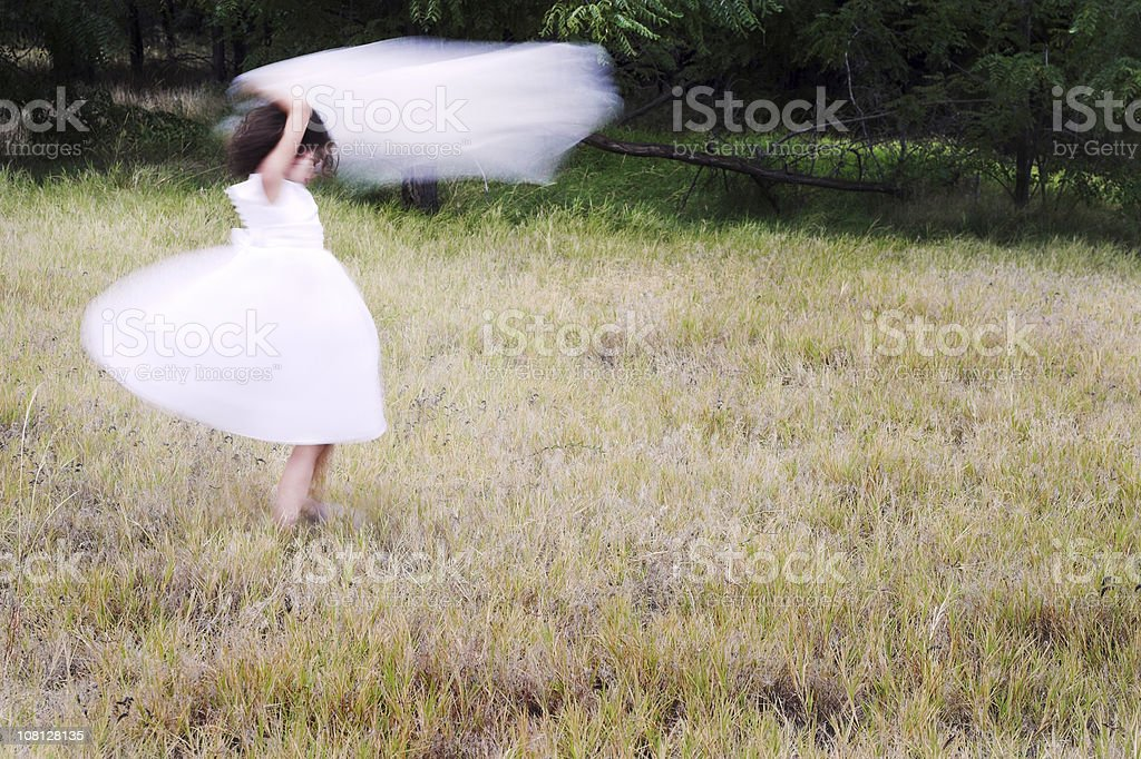 Little Girl Wearing White Dress and Spinning in Field royalty-free stock photo