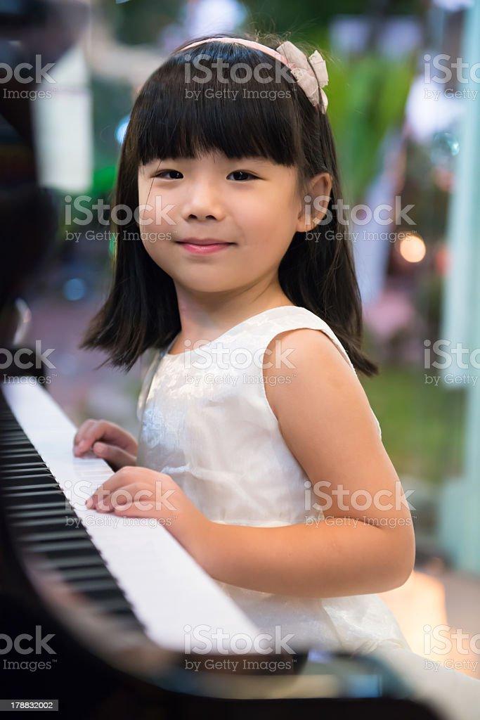Little girl wearing white dress playing piano stock photo