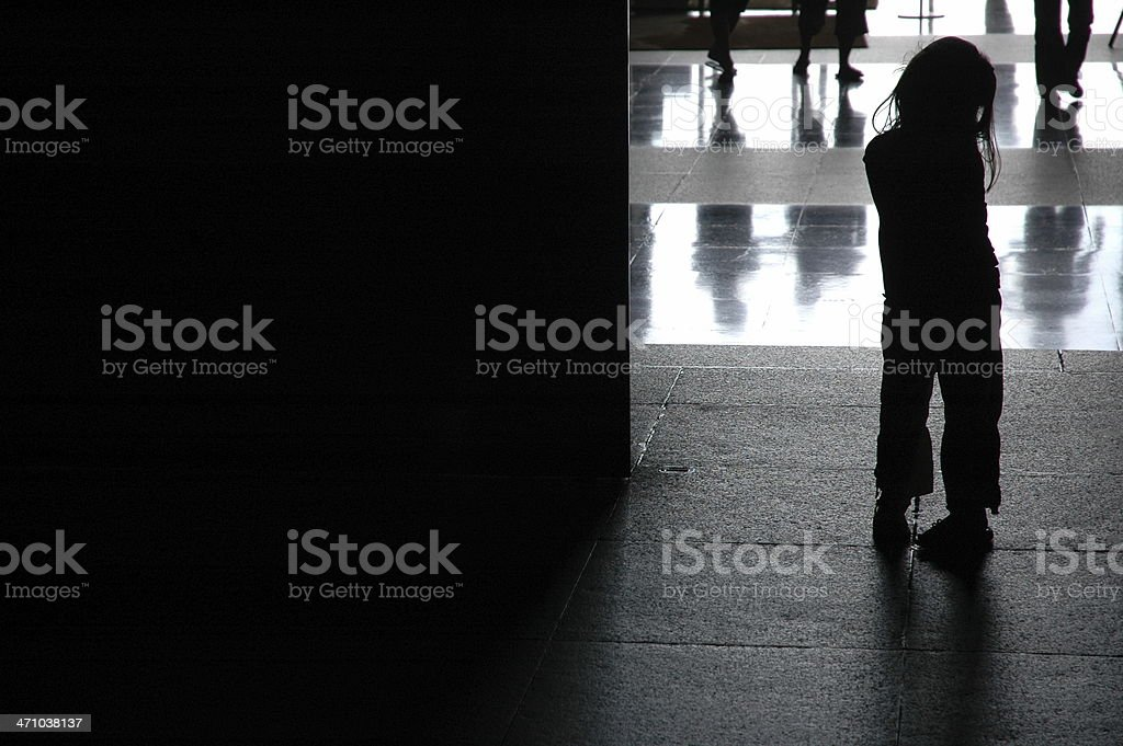 A little girl who seems to be lost in a large public place stock photo