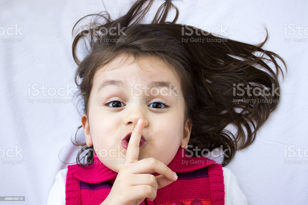 Little girl wispering and gesturing silence on bed stock photo