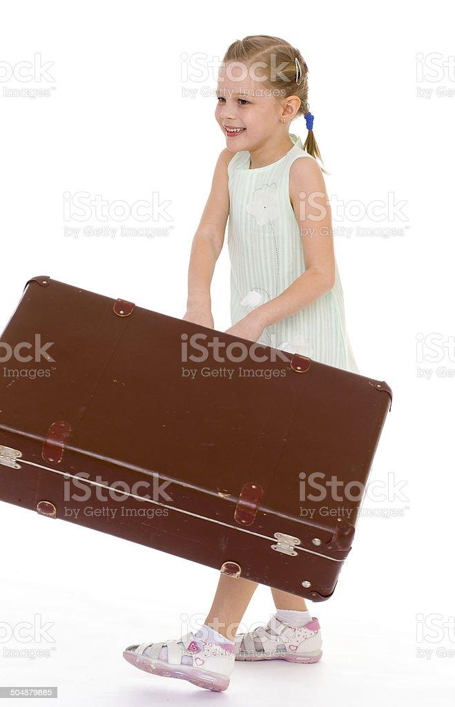 Petite fille avec un énorme et très vieille valise. photo libre de droits
