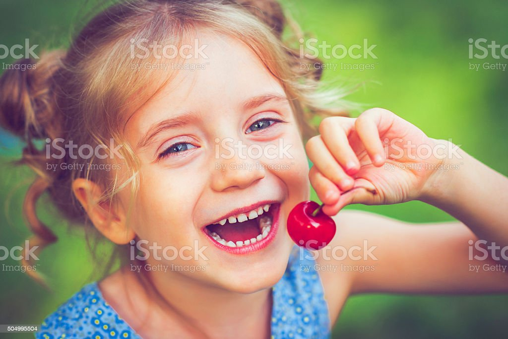 Little girl with a cherry stock photo