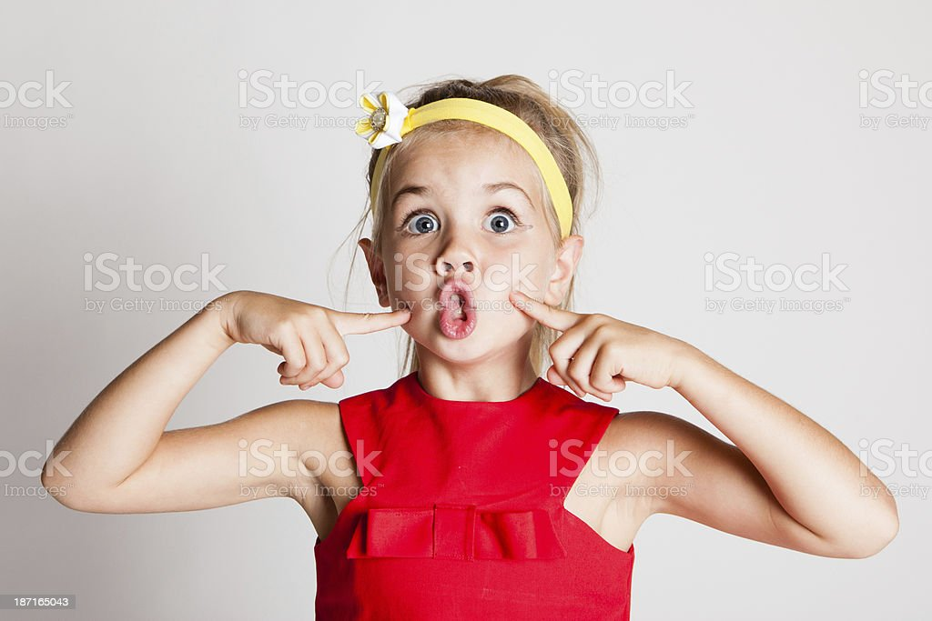 A little girl with a fish face pose stock photo