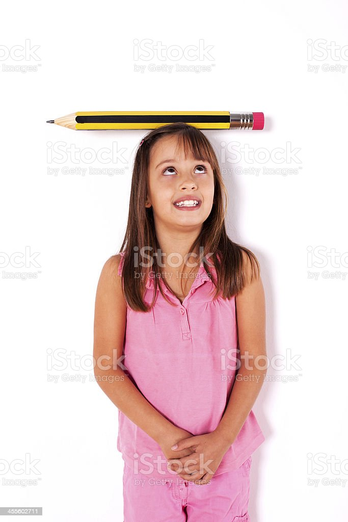 Little girl with a giant pencil over her head royalty-free stock photo