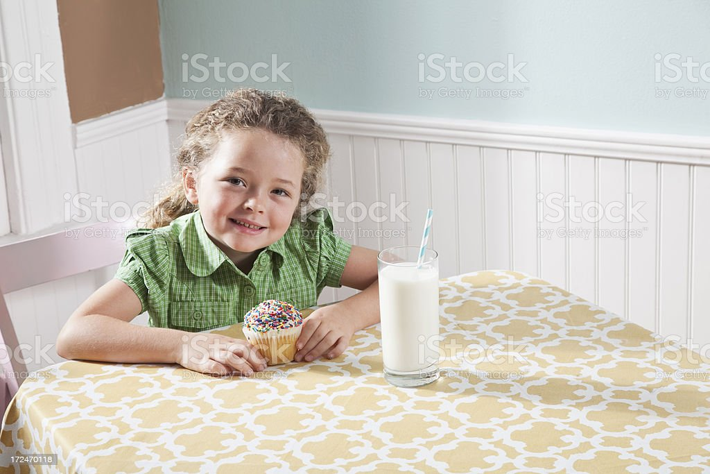 Little girl with a glass of milk and cupcake stock photo