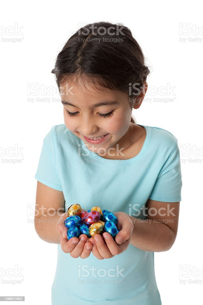 Little girl with a handful of chocolate eggs stock photo
