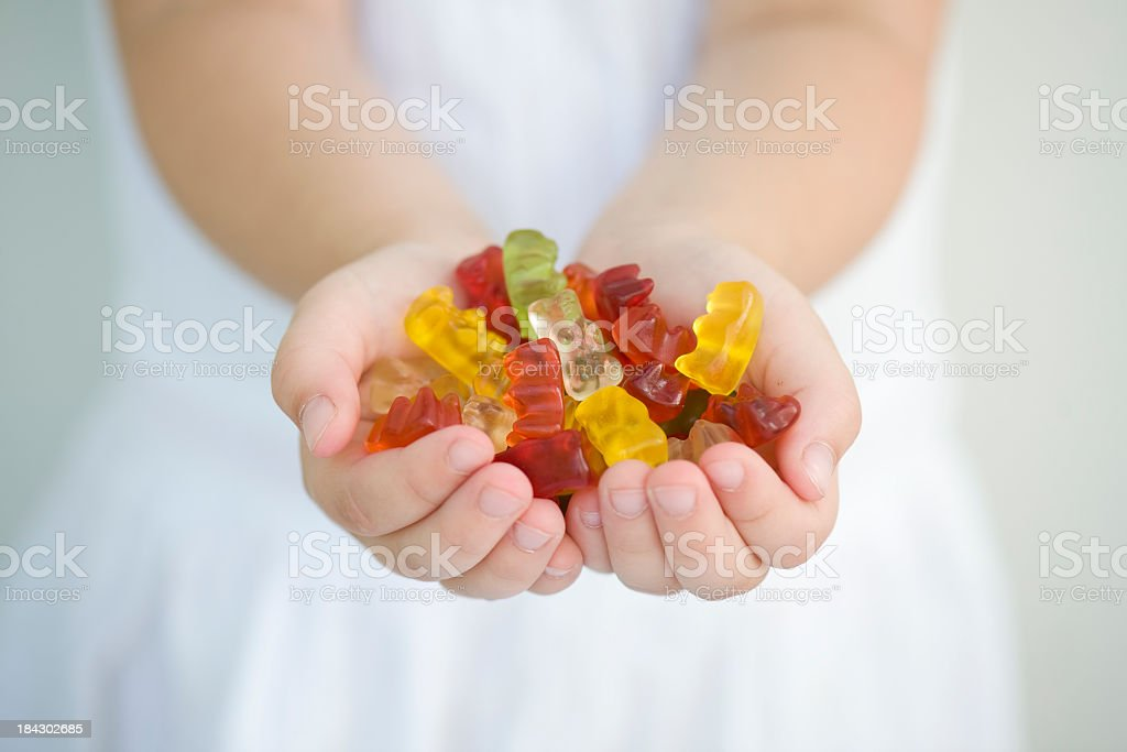 A little girl with a handful of gummy bears stock photo