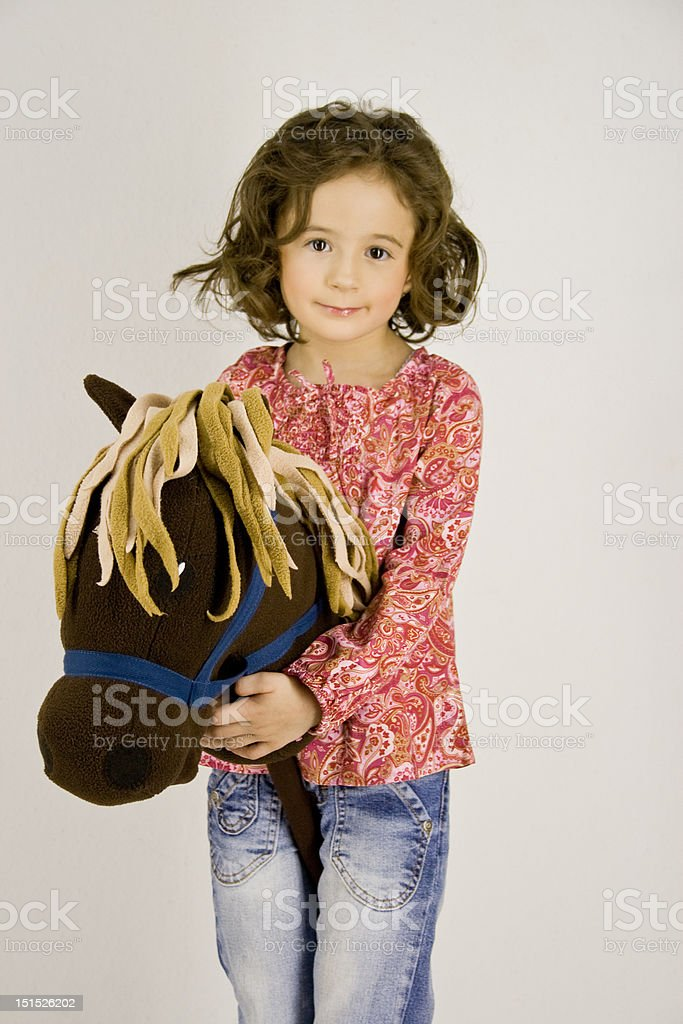little girl with a hobbyhorse royalty-free stock photo