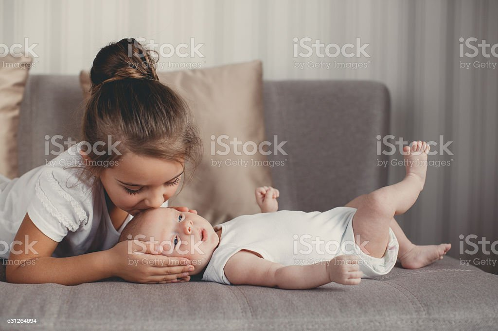Little girl with a newborn baby brother stock photo
