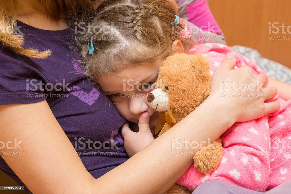 Little girl with a teddy bear clung to her mother stock photo