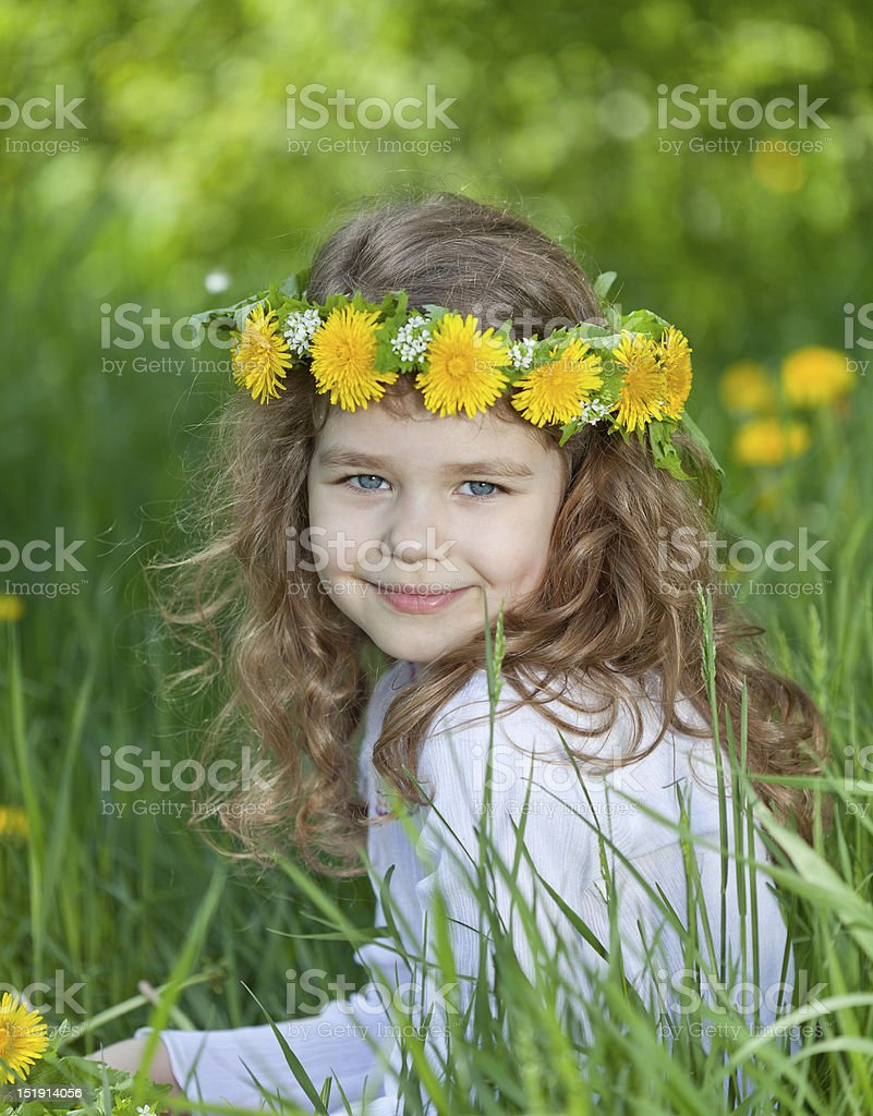 Little girl with a wreath of dandelions royalty-free stock photo