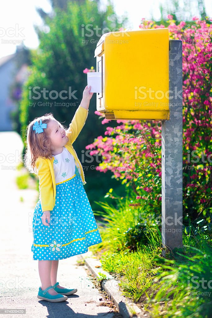 Little girl with an envelope next to a mail box stock photo