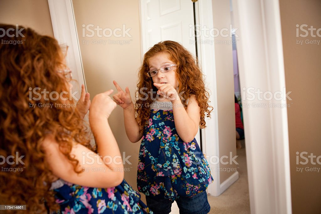 Little Girl With Attitude Talking To Herself in Mirror stock photo