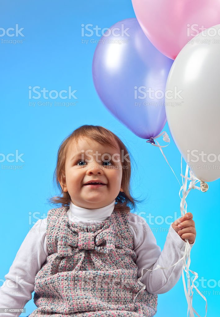 little girl with balloons on a blue background stock photo