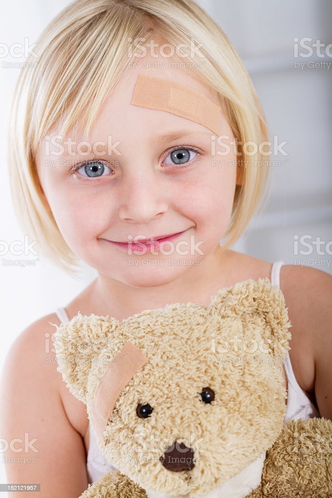 Little girl with bandaid in her forehead holding teddy bear royalty-free stock photo