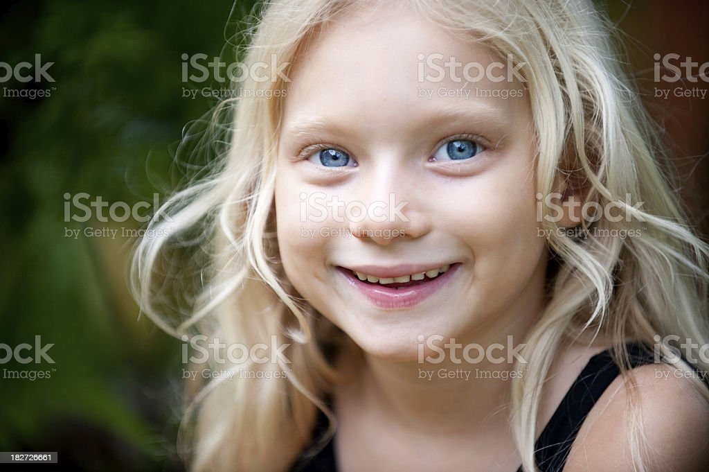 Little girl with big blue eyes and blonde hair stock photo