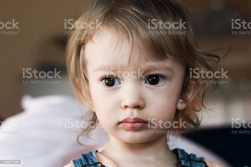 Little girl with big eyes staring at one point thinking royalty-free stock photo