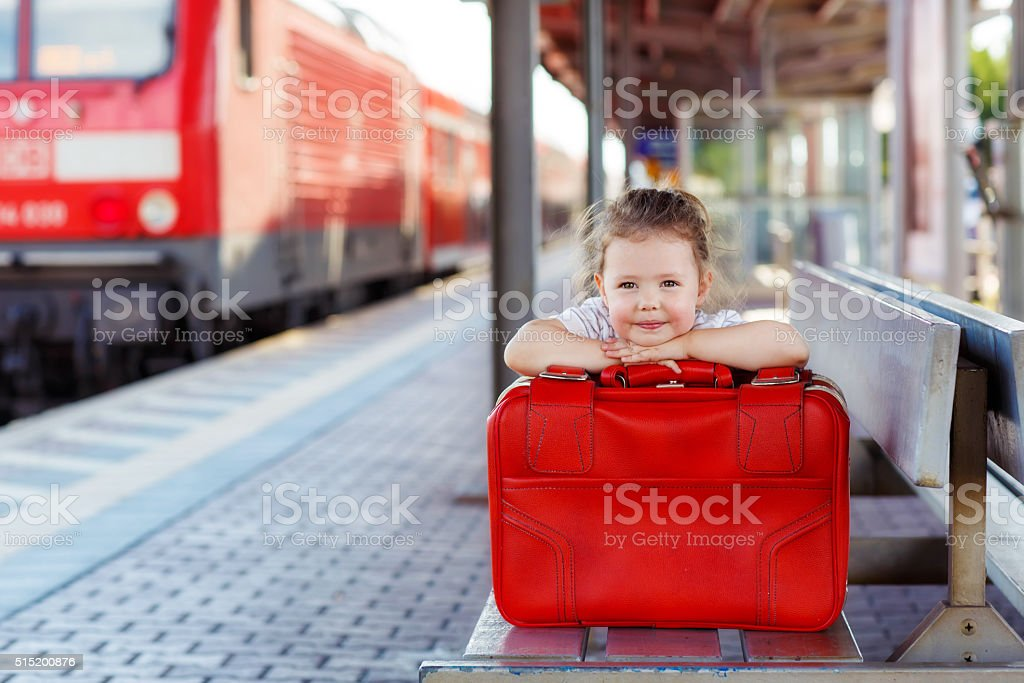 little girl with big red suitcase on a railway station stock photo