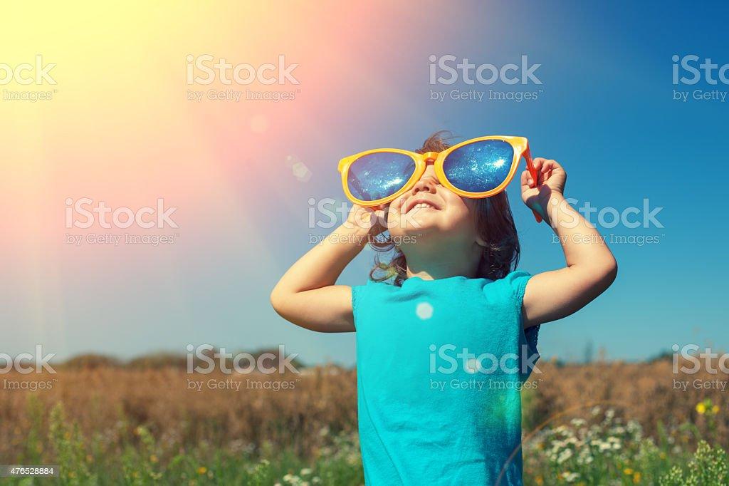 Little girl with big sunglasses enjoys sun stock photo
