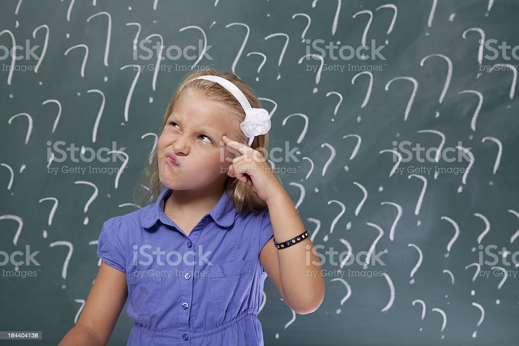 Little Girl With Blond Hair Thinking In Front Of Blackboard royalty-free stock photo