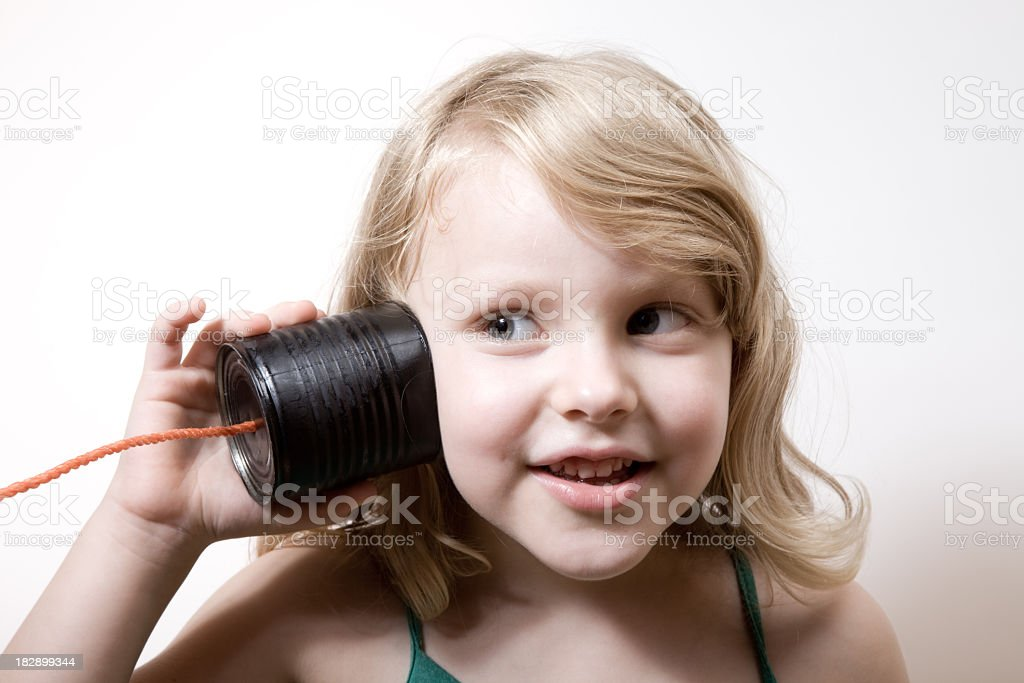 Little Girl With Blonde Hair Talking On Can Phone stock photo