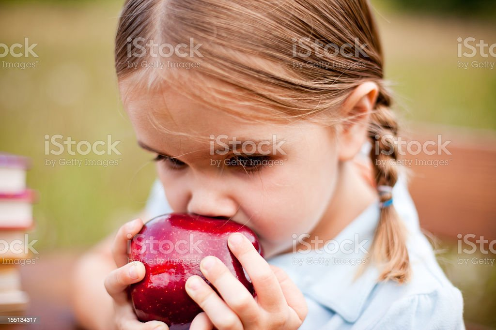 Little Girl with Braids Eating an Apple stock photo