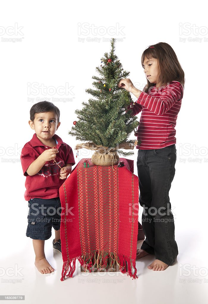 Little girl with brother decorating small Christmas tree royalty-free stock photo