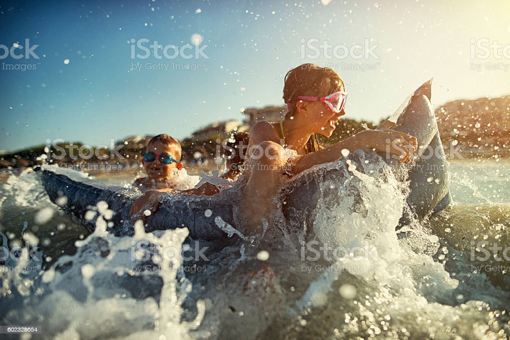 Little girl with brothers having fun in sea stock photo