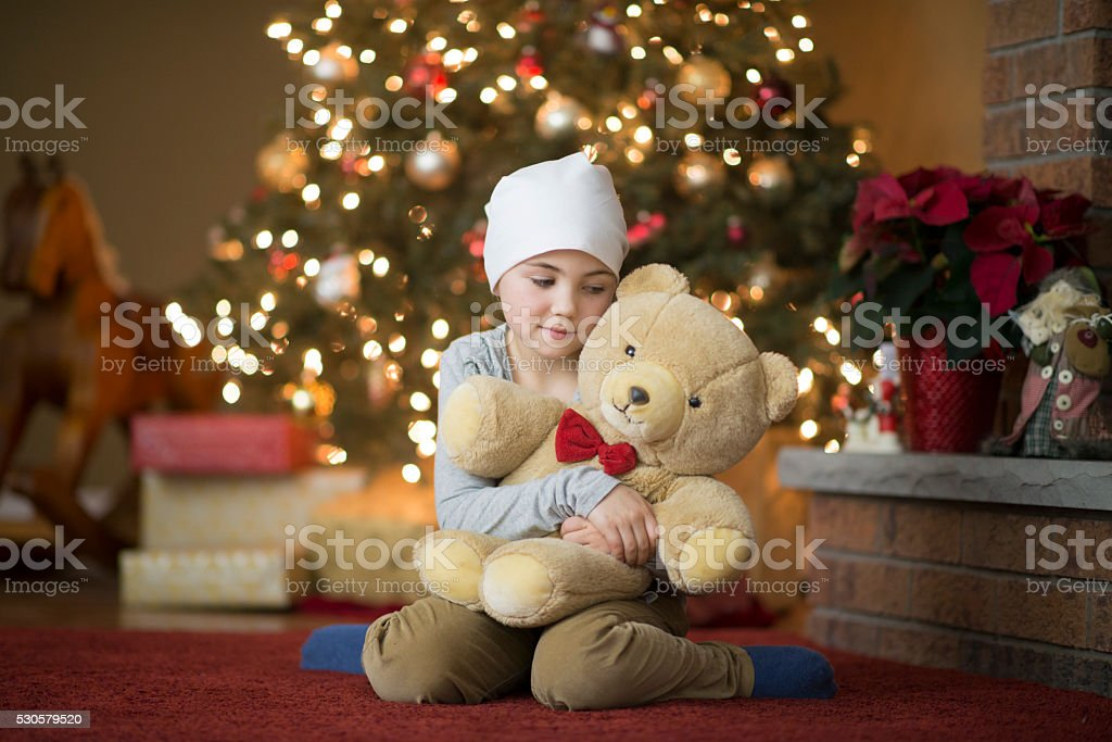 Little Girl with Cancer Holding Her Teddy Bear stock photo