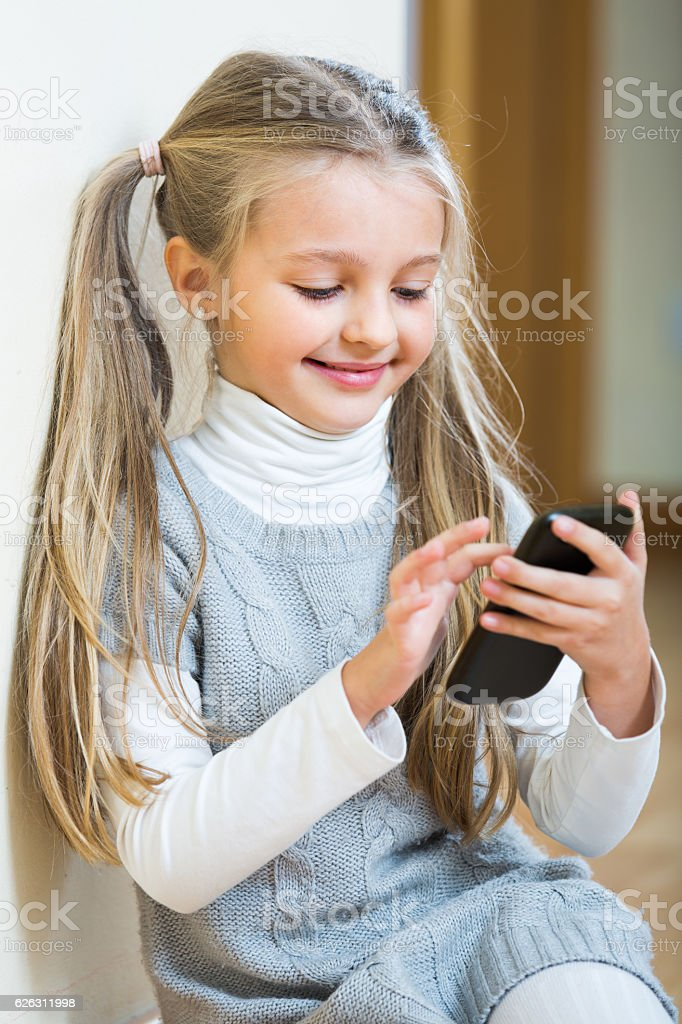 Little girl with cell phone indoors stock photo