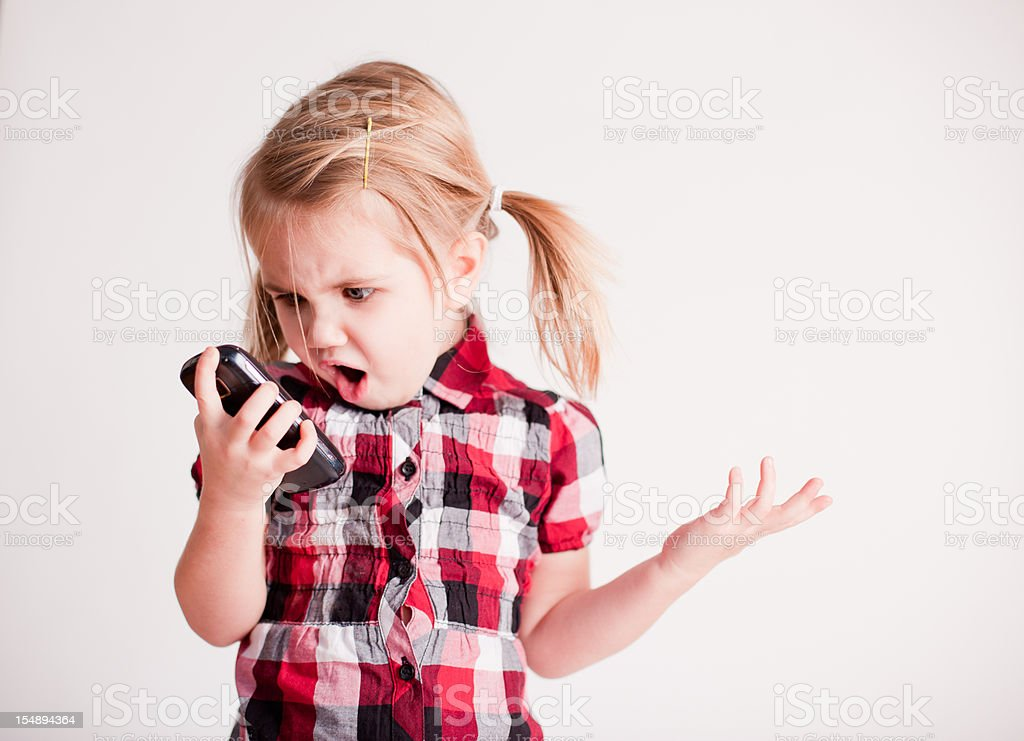 Little Girl with Cell Phone Showing Shocked Face stock photo