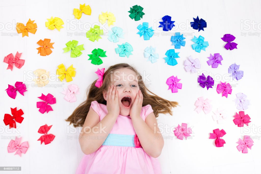 Little girl with colorful bow. Hair accessory stock photo
