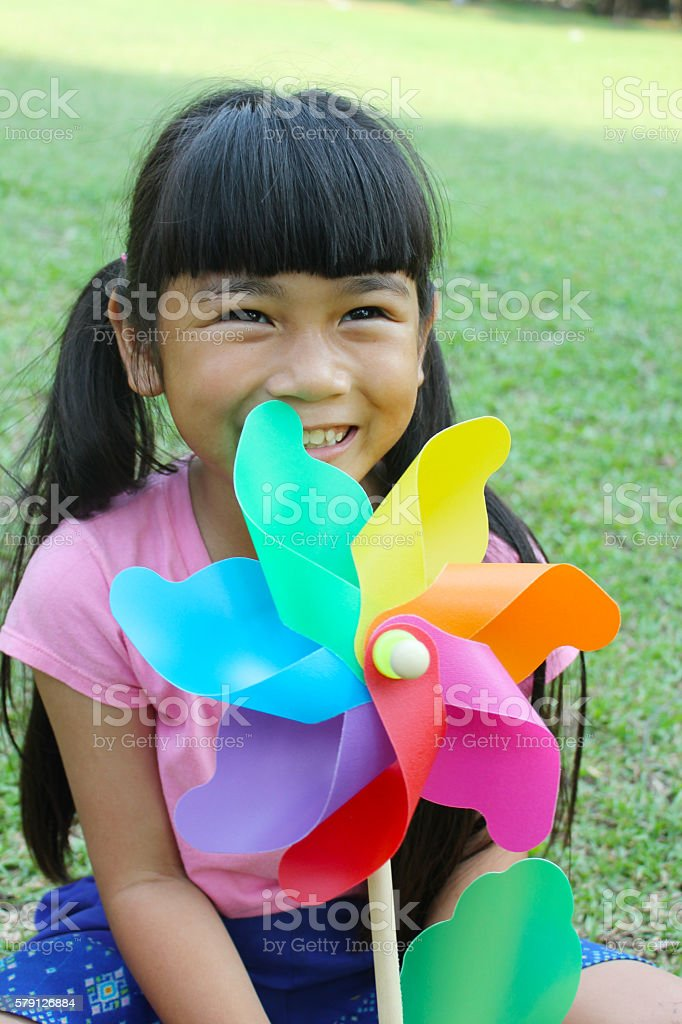 Little girl with colorful pinwheel in the park stock photo