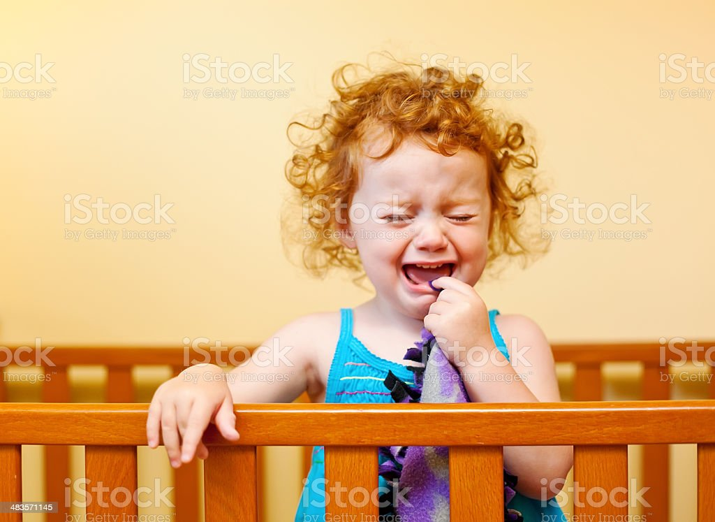 Little Girl With Curly Red Hair Crying in Crib royalty-free stock photo