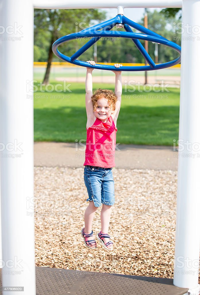 Little Girl With Curly Red Hair Hanging At Playground stock photo