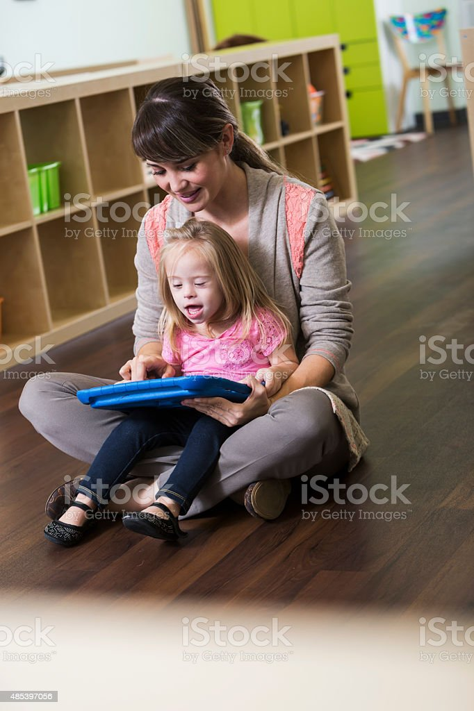 Little girl with down syndrome sitting on teacher's lap stock photo
