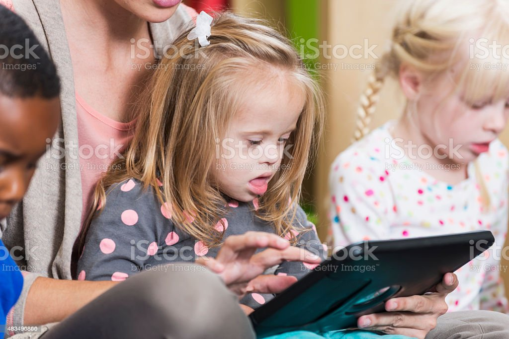 Little girl with down syndrome watching digital tablet stock photo