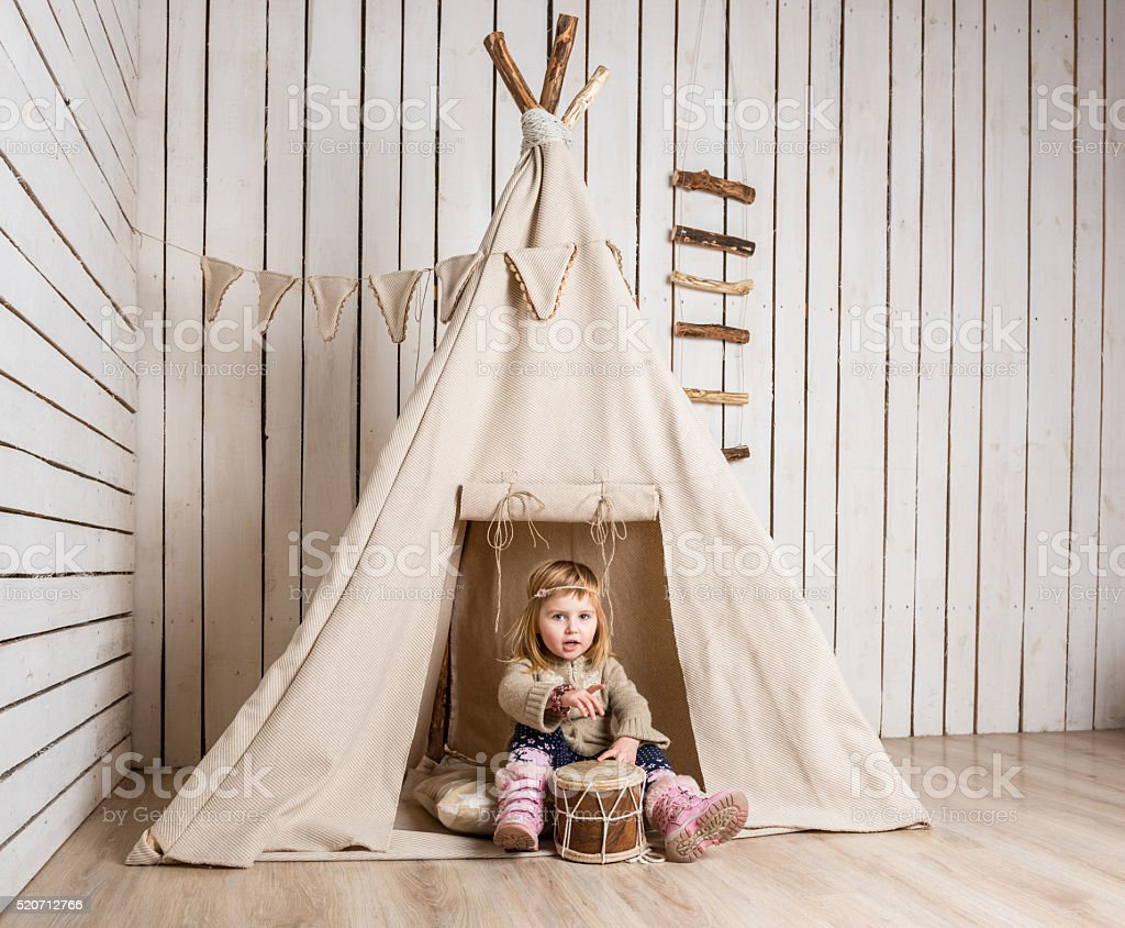 little girl with drum near wigwam stock photo