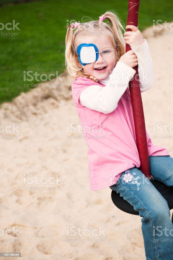 little girl with eye patch having fun stock photo