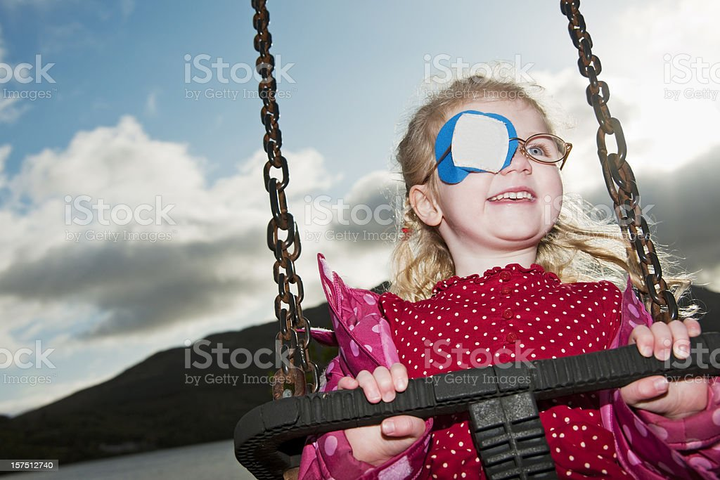 little girl with eyepatch having fun on swing royalty-free stock photo