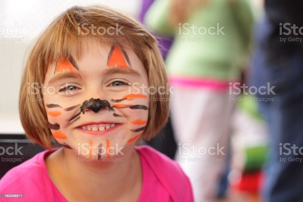 Little girl with face painted like tiger smiles at camera stock photo