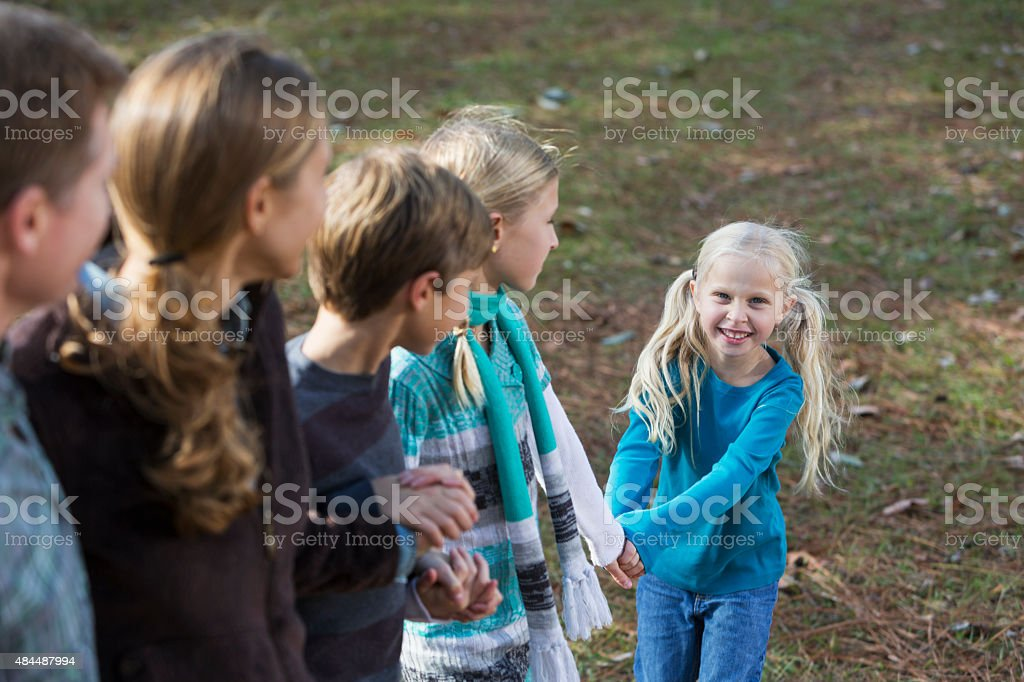 Little girl with family standing outdoors stock photo