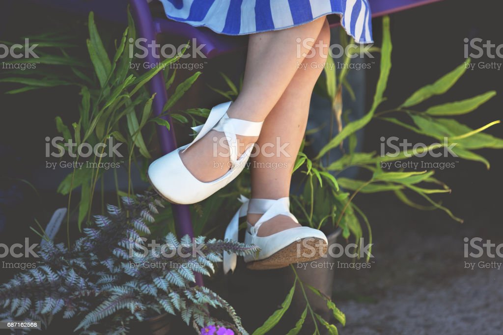 Little Girl With Fancy Shoes and Crossed Legs on Garden Bench stock photo