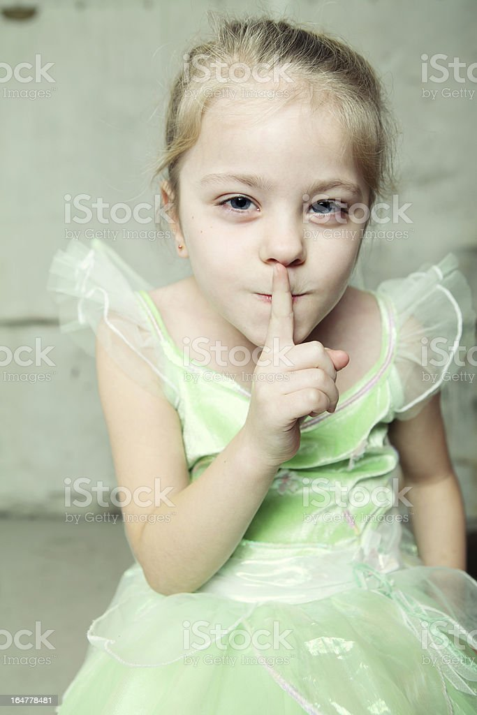 Little girl with finger to her lips stock photo