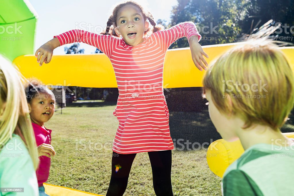 Little girl with friends jumping on bounce house stock photo